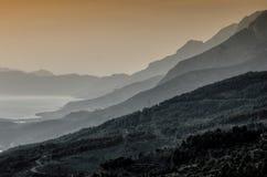 Pico de montaña en la puesta del sol sobre el mar fotos de archivo