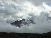 Pico de montaña que mira a escondidas a través de las nubes Foto de archivo