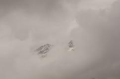 Pico de montaña a través de las nubes Fotos de archivo