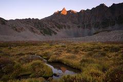 Pico de montaña en una luz roja y su reflexión en el agua Fotos de archivo