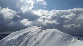 Pico de montanha contra nuvens com silhueta do homem Imagens de Stock