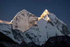 Pico de montanha de Kangtega em um nascer do sol da manhã na vila de Dingboche imagem de stock
