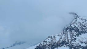 Pico de montanha nevado escondido em nuvens grossas, previsão de tempo, aviso da tempestade vídeos de arquivo