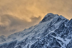 Pico de montanha nevado na luz impressionante foto de stock