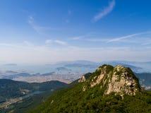 Pico de montanha rochosa, vila pequena circunvizinha, cidade, mar e ilhas Fotografia de Stock