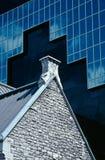 Pico de pedra do telhado da igreja de encontro ao arranha-céus moderno Foto de Stock Royalty Free