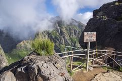 Pico do Arieiro hiking trail, amazing magic landscape with incredible views, rocks and mist, viewpoint with wooden railing. And wooden sign Royalty Free Stock Image