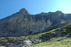Pico e cachoeira rochosos Grindelwald próximo em Suíça Fotografia de Stock