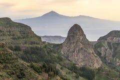 Pico Agando rock (La Gomera) and El Teide (Tenerife) Stock Image