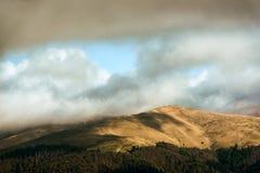 Pico hermoso en luz del sol debajo de las nubes Fotografía de archivo
