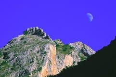 Pico montanhoso com lua e o céu azul fotografia de stock royalty free