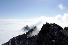 Pico sobre las nubes imagenes de archivo