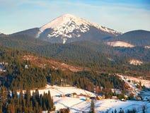 Pico y pueblo de la nieve de las montañas Foto de archivo