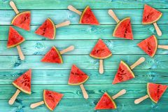 Picolés da fatia da melancia no fundo de madeira azul, conceito do fruto fresco imagem de stock