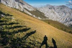 Picos,西班牙-小组远足者投下了在山的长的阴影 图库摄影