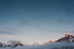 Picos alaranjados nevado da corrente de montanha no inverno Fotos de Stock