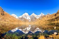 Picos altos cobertos de neve refletidos em um lago imagem de stock