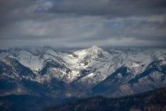 Picos cobertos de neve distantes nas serras foto de stock