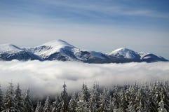 Picos coronados de nieve en la niebla Fotos de archivo libres de regalías
