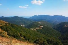 Picos das cordilheiras cobertas com a floresta verde imagens de stock