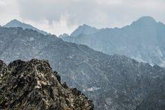 Picos de montaña bañados en nubes imagenes de archivo