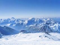 Picos de montaña blancos como la nieve en nubes Fotografía de archivo libre de regalías