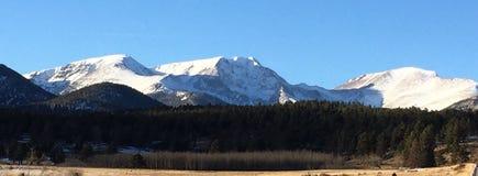 Picos de montaña contra el cielo azul claro Imagen de archivo