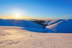 Picos de montaña cubiertos con la nieve y el hielo, en los cuales cae la sombra azul, contra el cielo azul Día escarchado, escena Fotos de archivo