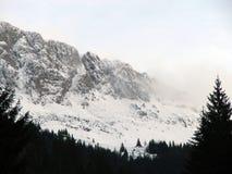 Picos de montaña cubiertos por las nubes y la nieve Fotos de archivo