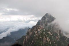 Picos de montaña en nubes Imagenes de archivo