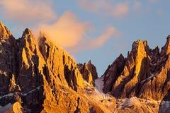 Picos de montaña hermosos cubiertos por las nubes coloreadas en la puesta del sol Foto de archivo libre de regalías