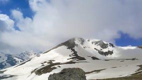 Picos de montaña majestuosos cubiertos con nieve y cielos azules de elevación imágenes de archivo libres de regalías