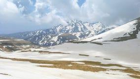 Picos de montaña majestuosos cubiertos con nieve y cielos azules de elevación imagen de archivo