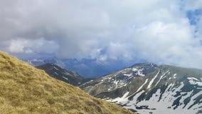 Picos de montaña majestuosos cubiertos con nieve y cielos azules de elevación imagenes de archivo