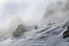 Picos de montaña Nevado en niebla fotos de archivo libres de regalías