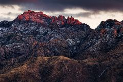 Picos de montaña nevados en la puesta del sol fotografía de archivo