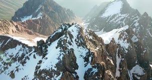 Picos de montaña rocosa cubiertos con nieve Tiroteo de un abejón, visión superior metrajes