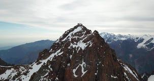 Picos de montaña rocosa cubiertos con nieve Tiroteo de un abejón, visión superior almacen de video