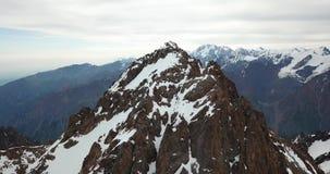 Picos de montaña rocosa cubiertos con nieve Tiroteo de un abejón, visión superior almacen de metraje de vídeo