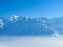 Picos de montaña sobre las nubes Imagen de archivo