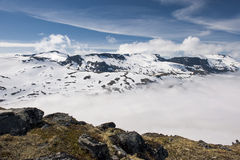 Picos de montanha acima das nuvens com céu azul e das nuvens brancas, vista da montanha Dalsnibba, Noruega Foto de Stock