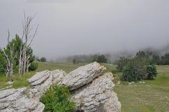 Picos de montanha das montanhas crimeanas cobertas com a névoa em um fundo do céu foto de stock