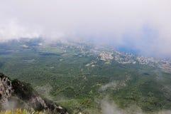 Picos de montanha das montanhas crimeanas cobertas com a n?voa em um fundo do c?u azul e do mar imagens de stock