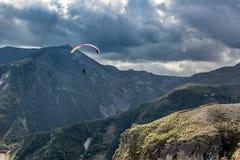 Picos de montanha em Geórgia O homem paira no ar em um papagaio Imagem de Stock Royalty Free