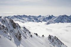 Picos de montanha nevado acima das nuvens fotos de stock royalty free