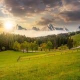 Picos rocosos detrás del bosque y del prado en la puesta del sol Fotografía de archivo