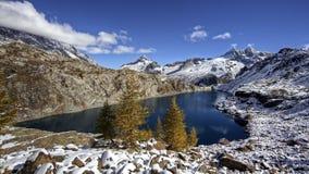 Picos y lago coronados de nieve de la montaña Reflexión de montañas coronadas de nieve en el agua del lago Paisaje de la montaña foto de archivo libre de regalías