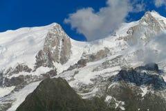 Picos y nieve rocosos en las montañas Foto de archivo