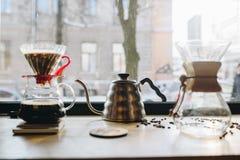 Picthers e feijões de café de vidro na mesa perto da janela imagens de stock royalty free