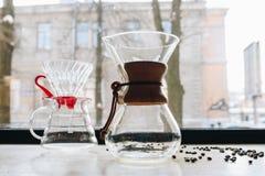 Picthers e feijões de café de vidro na mesa perto da janela fotografia de stock royalty free